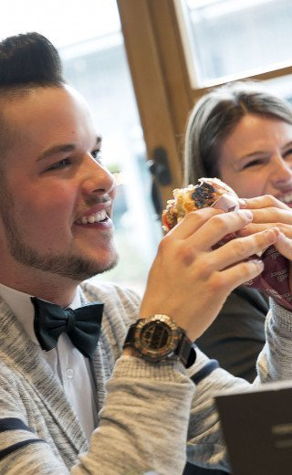 "A young man is eating an juicy burger at the ""Pöstli Corner"" in Davos"