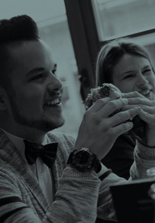 "A young man is eating a juicy burger at ""Pöstli Corner"" in Davos"